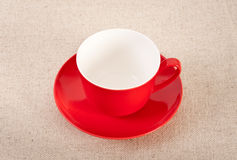 Empty red coffee cup on canvas background. Empty red coffee cup and saucer on canvas background Stock Photos