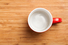 Empty red coffee, tea mug, cup, top view on wood. Top view on empty red coffee or tea mug or cup. Studio shot from above on wooden background, underground Royalty Free Stock Image