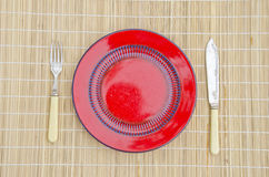 Empty red dinner plate with knife and fork Stock Image