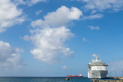 Empty Red Freighter Beyond White Cruise Ship. White Luxury Cruise Ship Docked at St Croix Stock Photos