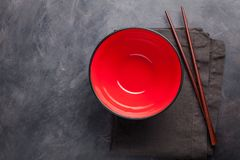 Empty red glass bowl of Chinese noodles and wooden sticks on dark concrete background. Top view with copy space. Flat lay royalty free stock image