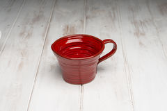 Empty Red Handmade Cup on White Wooden Panel Surface Stock Image