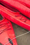Empty red plastic recreational kayaks for rent or hire, stored on sandy beach after hours on a rainy day. Crescent Beach, Surrey, stock image