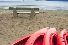 Empty red plastic recreational kayaks for rent or hire, stored on sandy beach after hours on a rainy day. Crescent Beach, Surrey, royalty free stock images