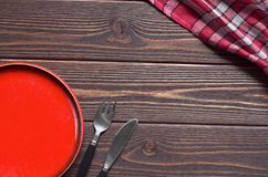 Plate and cutlery. Empty red plate and cutlery on brown wooden table, top view. Space for text Stock Photography