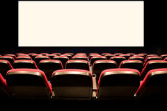 Empty red seats in a cinema. Backs of empty red seats in a movie theatre with a white screen Royalty Free Stock Images