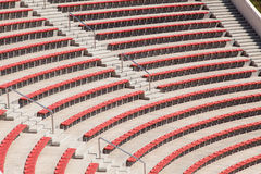 Empty red seats on football stadium or amphitheater. Empty plastic red seats on football stadium or amphitheater Royalty Free Stock Photos