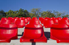 Empty red stadium seats. In an open space Stock Image