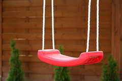 Empty red swing Stock Photos
