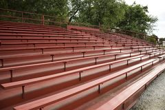 EMPTY RED WOODEN BLEACHERS. Red wooden bleachers wait for the fans to come and cheer on their team royalty free stock photo
