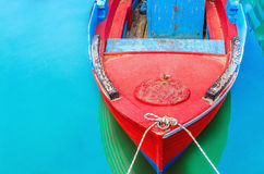 Empty red wooden boat with blue broadside moored in port with s Stock Image