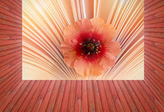 Empty red wooden deck table with beautiful little flower in a book background. Ready for product display montage. Aroma of story Royalty Free Stock Photography