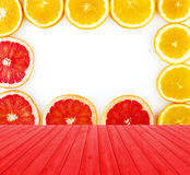 Empty red wooden deck table with fresh grapefruit and oranges rings set isolated on white background with copy space. Stock Image