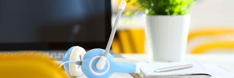 Empty remote office workplace with laptop and headset Royalty Free Stock Images