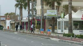 Empty resort town street at low season. Few local people walking on sidewalk. Stock footage stock footage