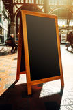 Empty restaurant menu street black chalkboard as copy space. Unrecognizable people in the background Stock Photos