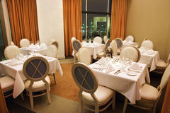 Empty Restaurant Seating. Empty seats in a restaurant dining area with a night time view shown through an open curtain in the background. Horizontal shot Stock Photo