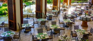Empty Restaurant Tables and Chairs Awaiting Gueststy. Empty tables with place settings waiting for mid day diners to show. Banquet style plates are stocked on royalty free stock images