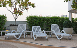 Empty resting chair near children swimming pool in hotel  Royalty Free Stock Images