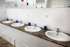Empty restroom public men bathroom interior with washing hand sinks. stock images