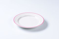 Empty rimmed dinner plate. Rimmed dinner plate with pink colored edge Royalty Free Stock Photo