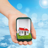 Empty ring box with house in humans hand Stock Image