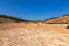 Empty river-bed in a dry dusty landscape. With distant trees on the horizon Royalty Free Stock Photo
