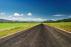 Empty road. Green field and blue sky Royalty Free Stock Photography