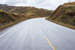 An empty road across barren hills of upper Tibet region Royalty Free Stock Photos