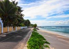 Empty road along the ocean`s beach, Mahe, Seychelles Stock Images
