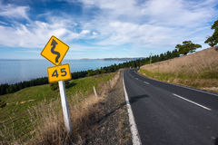 Empty Road by the bay with speed limit and winding road sign in New Zealand. Royalty Free Stock Photo