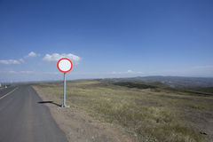 Empty road and blank traffic sign at windmill farm Stock Photos