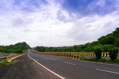 Empty road borded by  hills with cloudy skies Stock Photos