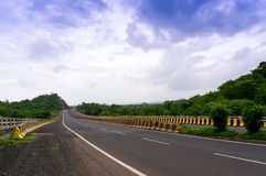 Empty road borded by  hills with cloudy skies Stock Image