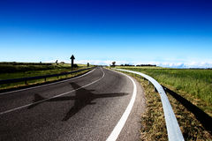 An empty road in the campaigns with a blue sky, plane shadow Royalty Free Stock Photo