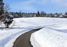 Empty road cleared of snow. High snow banks by side of road leading up a hill after recent plowing royalty free stock image