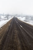 Empty road in a cold foggy winter day. Empty road with lines, in a cold foggy winter day royalty free stock images