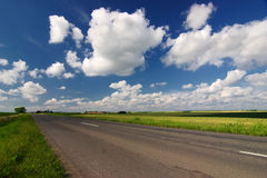 Empty road through countryside with beauty clouds Royalty Free Stock Photo