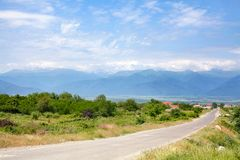 Empty road in the countryside, mountains on the horizon and blue sky with clouds background stock photography