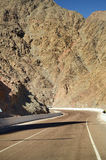 Empty road crossing an arid mountain. In desert Royalty Free Stock Photo