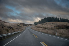 Empty road curving to the right at dusk. Under a darkening sky Royalty Free Stock Photography
