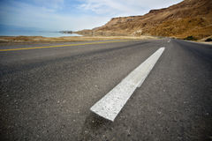 Desert Asphalt Road. An empty road in the desert, shot with a low and very wide angle. The Sodom mountains are seen in the horizon, and the Dead sea is just to Royalty Free Stock Photo