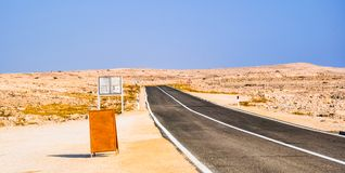 Empty road through the desert. Wooden blank sign on the left side of the photo royalty free stock photo