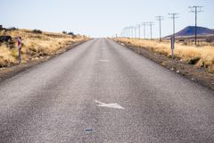 Empty Road with Direction. Empty tar road on a slope and white direction arrows and road signs Stock Images