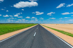Empty road on either side  fields. Empty road on either side cultivated fields Stock Photo