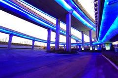 Empty road floor with city viaduct bridge of neon lights night Stock Photos