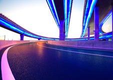 Empty road floor with city viaduct bridge of neon lights night Stock Image