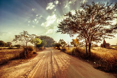 Empty road going through rural landscape under sunset sky Stock Photos