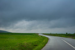 Empty road through green fields Royalty Free Stock Image