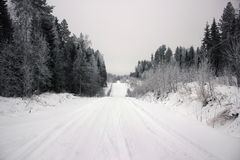 Empty road with huge snow banks on sides on cloudy winter day. Empty road with huge snow banks on sides on cloudy winter day royalty free stock photography